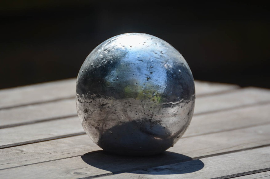 Silver ball on a table. Beautiful reflections.