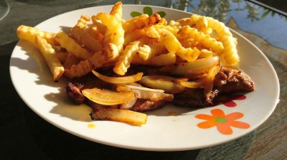 French Fries And Steak With Onions