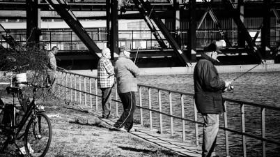people photography - fishing near the bridge
