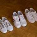 three pairs of white sneakers